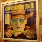 """Табела предупреждение на стената в тоалетна в информационен център край пътя. Надписът гласи: """"Твоят следващ принудителен шофьор - Ако пиеш и караш, ние ще те повозим. До затвора."""" Има и пояснение от устата на шерифа, че на пиян шофьор в Тексас може да му излезе до 17 000 долара в глоби, такси за адвокати и др. Снимка: Иван Бакалов"""